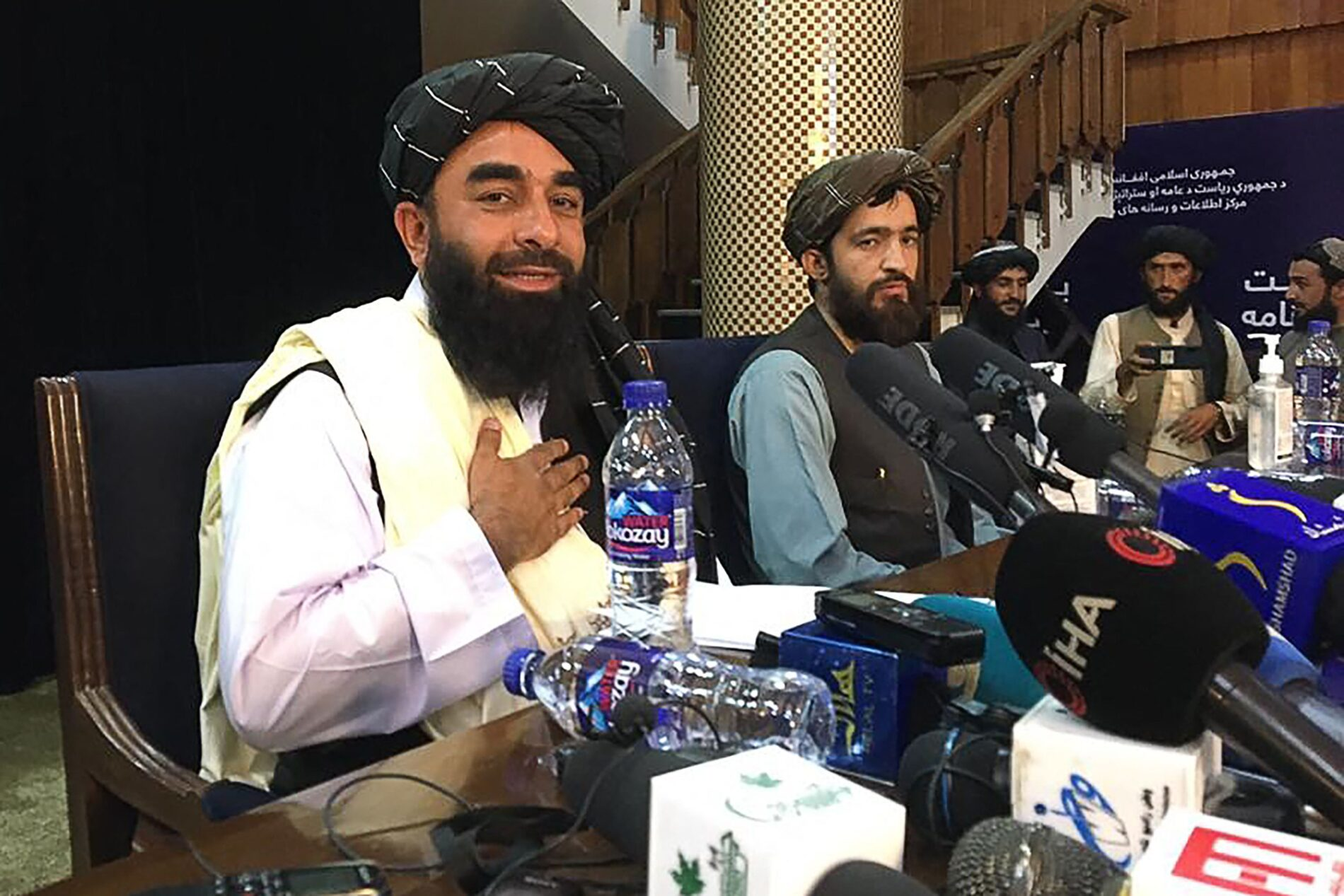 Taliban spokesperson Zabihullah Mujahid (L) gestures as he arrives to hold the first press conference in Kabul on August 17, 2021 following the Taliban stunning takeover of Afghanistan. (Photo by Hoshang HASHIMI / AFP)